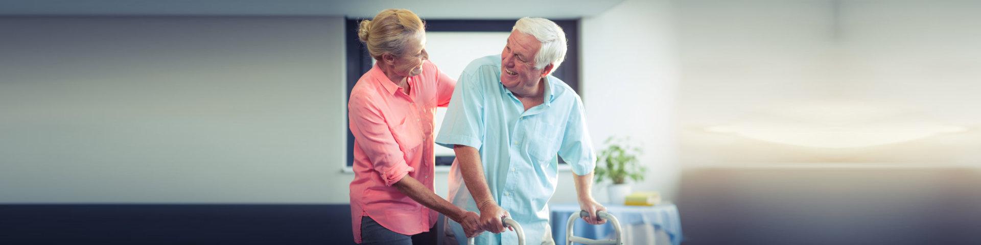 senior women helping senior men to walk