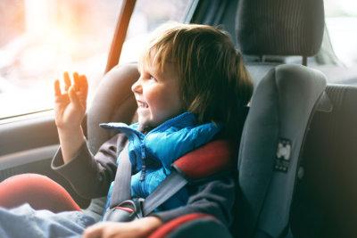 pretty toddler boy sitting in car seat
