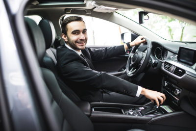 young man in suit driving car